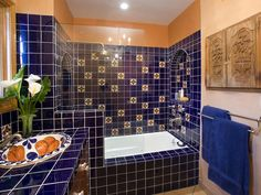 Latin flavor makes a splash in the bathroom with vibrant, handpainted tiles. Designer Erica Islas creates a traditional, Mexican-style bathroom with a custom sink and vanity, surrounded by detailed tile work.