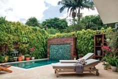 """Acompanhada por uma cascata e uma parede verde, a """"piscina de estar"""" se tornou o centro das atenções neste jardim em uma casa paulistana. Projeto Gigi Botelho."""