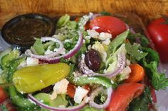 Greek Salad: Lettuce, Tomatoes, Cucumbers, Carrots, Green Peppers, Red Onions, Pepperoncini, Greek Olives, topped with Feta Cheese & our Homemade Greek Dressing.
