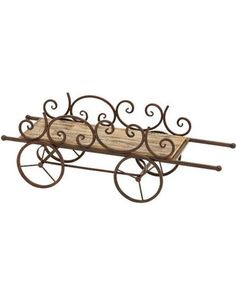 Cart-inspired metal plant stand with a wood shelf and scrollwork accents. Product: Plant stand Construction Material: Wood and metalColor: Natural and bronzeFeatures: Scrollwork accentsDimensions: H x W x D Wood And Metal, Metal Art, Home Decor Accessories, Decorative Accessories, Metal Bending Tools, Metal Plant Stand, Garden Cart, Wood Planters, Garden Supplies