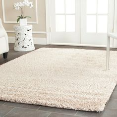 Bring luxuriously cozy comfort to any floor of your home with this casual beige shag rug. Crafted from durable high-density polypropylene, this power-loomed rug with a plush one-inch pile provides easy warmth youll love to curl your toes in.