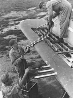 Armorers loading belts of .50 caliber ammunition into the four ammo trays in one wingtip of a P-47 thunderbolt.