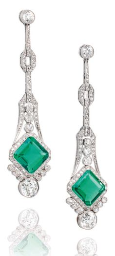 A PAIR OF ART DECO EMERALD AND DIAMOND EAR PENDANTS, CIRCA 1920. Millegrain-set throughout, each composed of an articulated single-cut diamond collet line and geometric panel surmount, suspending a square-cut emerald, within a similarly-set diamond border, to a collet drop terminal, post fittings, circa 1920, 5.9cm.
