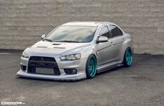 Mitsubishi Evolution X...love the teal coloured rims.. looks too low however.. would be annoying driving a car that lowered.