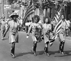 Color Guard members of the Quaker City Drum and Bugle Corps add  to the festivities in Philadelphia's Labor Day Parade, 1941.  A black and white photograph depicting four African American women walking in color guard garb displaying American flags. Observers are lining the sidewalk in the background.  (Special Collections Research Center, Temple University Libraries)