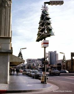 "Dec. 1963: Looking SE from Hollywood Blvd/McCadden Place towards the Egyptian Theater, which had just held a premiere for Otto Preminger's film, ""The Cardinal"". Note the lack of ficus trees along Hollywood Blvd-except for the seasonal Christmas tree lamps that adorned each street light at that time."