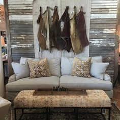"""A collection of vintage chaps as art. They are hanging over a slipcovered #leeindustries sofa. We threw in an antique rug bench and some of our """"in-house-made"""" pillows. #simplethingsfurniture #fortworth by simplethingsfurniture"""