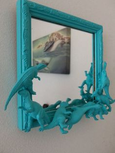 This teal blue dinosaur mirror is so fun and cool! And with a few old dino toys and a glue gun, we bet you could make one, too! #DIY #dinosaurs #dinotheme #kidsrooms #playrooms #mirror