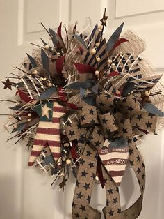 This primitive Americana patriotic wreath is made of ivory and cotton burlap deco mesh. I then accented with a burlap navy striped ribbon and Americana canvas stripe ribbon throughout. I added a primitive American Wood Star and a primitive Americana wood Heart that says Life Liberty and Happiness. Then I added ivory pip berries that are accented with rusty stars. Windowpane mesh throughout adds to this wreath. I then tied it all together with a canvas ribbon accented with navy blue stars…