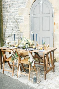 This Tuscan-inspired table is all rustic elegance. A centerpiece on ash wood of peach blossoms, navy tapered candles, and scattered fruits set against pale brick walls and a distressed door call to mind a pastel harvest.