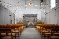 warehouse wedding ceremony setup using antique wood backdrop & strung patio lights