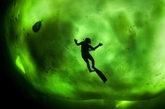 Underwater Photographs Of Northern Lights Reflected Beneath Russia's White Sea.