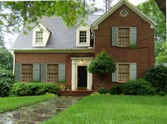Red brick house, black door, cream trim, light blue shutters--maybe this intensity of green shutters and door? deep green shade of living room color Shutters Brick House, Red Shutters, House Windows, Up House, House Front, Cozy House, Front Porch, Exterior House Colors, Exterior Paint