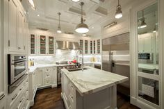 Beautiful kitchen with polished nickel picture lights illuminating glass-front upper cabinets and inset lower cabinets paired with white and grey marble countertops and white marble backsplash.
