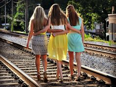 Group of friends walk down railroad train track. Best friends photo shoot ideas. Senior photo