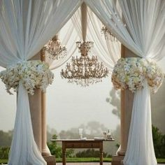 Gazebo with ivory fabric and wildflower style flower clusters
