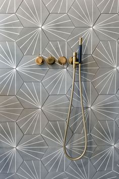 Shower wall with grey hexagon cement tiles with white dandelion inspired pattern. The brass fixtures completes the look. Design by Kodde Architecten Cement Tiles Bathroom, Bathroom Tile Designs, Bathroom Interior Design, Bathroom Flooring, Bathroom Fixtures, Brass Bathroom, Kitchen Tile, Wall Tiles Design, Bathroom Cabinets