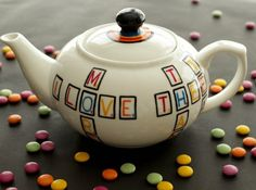 """Large Teapot from the Scrabble collection. Rainbow heart on one side and message on the other: """"You are my one true love"""" Hand Painted Ceramics by artist Caro Spinette. Photo by Kate Sims"""