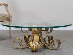 "The extravagant flared shape of this vintage French cocktail table makes a powerful visual statement. Five iron sections have been hand forged to achieve their unique shape and gathered together with a single iron strap around the centre. The original gilded finish has aged beautifully to create a distinctive pattern that is pleasing to view from any direction. Because of the scale of the gilded iron the table has a circular piece of 3/4"" glass on top allowing full viewing of the base."