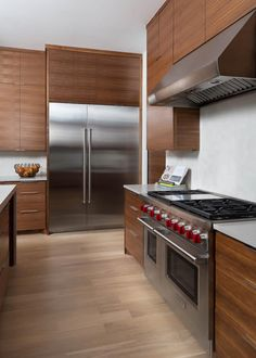 Modern Kitchen With Flat Front Walnut Cabinets and Stainless Steel Appliances