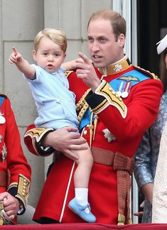 Prince George of Cambridge is held by Prince William, Duke of Cambridge as they look out from the balcony of Buckingham Palace during the Trooping the Colour on June 13, 2015 in London, England. Prince George is wearing the same outfit that his father, Prince William  first wore at Trooping the Colour in 1984.