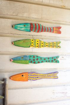 "Made in Haiti, this colorful set of fish are constructed from hand painted recycled wood. Each fish is outfitted with two metal hooks which makes wall hanging a breeze. Hardware not included. each is approx 22"" x 3½""t"