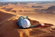 Sahara. Repos d'un Touareg au sommet de Tin Merzouga, la plus grande dune de la la Tadrart Algérienne. Les dunes de Merzouga forment un des plus beaux endroits au monde. Photo: Evan Cole.