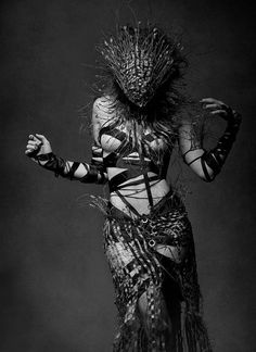 Not quite sure what strikes me about this image... The wooden maskthing or the outfit of straps. Yum!