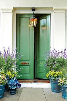 A beautiful bold green front door paired with planters filled with purple flowers and green foliage. #frontporch #porchdecor
