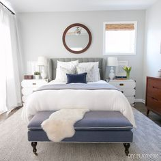 A white neutral bedroom with pops of navy. Love this city bedroom.