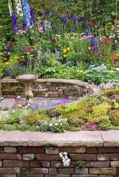 Colorful mixed perennial flower garden with Delphinium, sempervivum rock garden, bird bath, and climbing plants, circular sunken patio, rais...