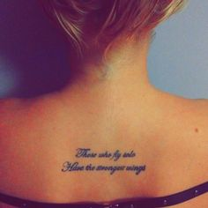 Upper back tattoo saying 'Those who fly solo have the strongest wings' on Jenny.