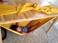 Why not be the cool mom who shows her kids how to make one of these. :)  Under the table hammock. Best if you hook opposite corners of the table to hold the weight evenly.