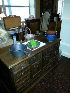 This sink unit for an American Girl sized doll started life as a wooden jewelry box.  I cut a hole to inset the ceramic square bowl.  Also drilled holes for the copper icemaker tubing which is bent to resemble a faucet.  The  faucet handles are drawer pulls.  I still plan to paint the unit and add a topper out of vinyl tile to match the stove unit.