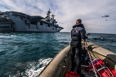 A Sailor stands watch near USS Boxer. by Official U.S. Navy Imagery