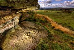 Rock art in Northumberland, England. Featuring a mysterious mix of concentric circles, interlocking rings and hollowed cups, they are broadly dated between 4,000 and 6,000 years old. They may have been used in feasting or as part of a ritual, perhaps even as territorial markers or 'signposts'. The precise meaning of the carvings remains a delicious mystery. Photo: Brian Kerr