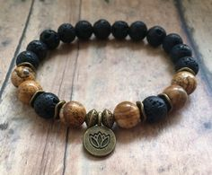 Lava Rock Energy Bracelet, Root Chakra Bracelet, Negative Energy Amulet, Lava Rock Jewelry, Essential Oil Diffuser Bracelet, Yoga Bracelet. This handmade Beaded Bracelet is made with 8mm Black Lava Rock and Picture Jasper Stones with Brass Wavy Spacers and a Brass Lotus Flower Charm. It