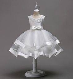 Beaded Tiered Dress-Beautiful & Cheap Round Neckline Sleeveless Knee Length Tiered Layered Infant Toddler Little & Big Girl Party Dress. Available from 3 - 9 years. Materials: Cotton, polyester, tulle mesh. Colors: Pink, Royal Blue, Red, Champagne & White. Please do compare your little girl's measurements with our size chart (Fits smaller than usual).