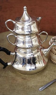 Stacking set of 2-cup teapot, milk jug and sugar bowl made of silver coloured metal with a punched hole decoration and faux ebony handle