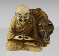 """JAPANESE CARVED IVORY NETSUKE MAN WITH TIGER Late 19th century carved ivory netsuke of man, seated in lotus pose, with tiger, signature to bottom. Weight: 29g Size: 1.5 x 1.5 x 1"""""""