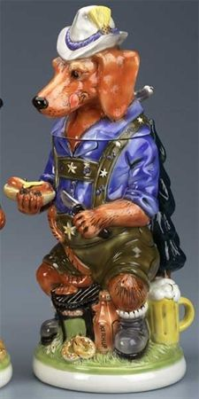 """The 10th edition to the Man's Best Friend Series. A Bavarian theme a Dachshund is the setting in which a Dachshund is dressed in lederhosen and suspenders with hat and knapsack. In the Black Forest grilling a string of """"wieners"""". A full stein of beer, a bottle of ketchup and pretzels, a jar of sauerkraut, onions. The handle is in the shape of a Black Forest evergreen tree. Limited edition of 5,000 pieces."""