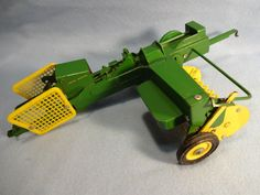 """Vintage Die Cast John Deere Ejector Square Baler for a tractor. It is 1/16th scale, made by Ertl Company, Dyersville, Ia. USA, original John Deere Green & Yellow paint and is 14 1/4"""" long x 6 1/4"""" wide. It has a metal frame, bale chamber and """"crank hitch"""". The head is also metal and has plastic pickup teeth & bale cage, flywheel and wheel rims. It is all complete and in good working condition. John Deere graphics are on each side and are in good condition."""