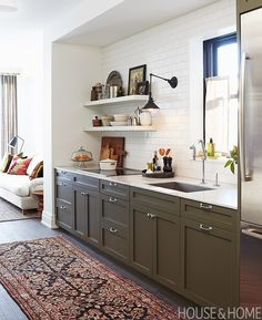 Shaker-style cabinets painted Dark Olive (2140-30) by Benjamin Moore introduce contrast in the otherwise white space. | Designer:  Mandy Milks & Mazen El-Abdallah Photographer:  Michael Graydon