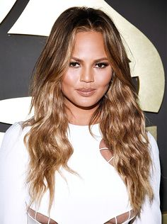 Chrissy Teigen's sun goddess vibes with beachy waves and a bronzed glow.