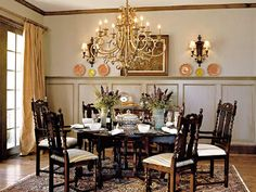 This dining room occupies the opposite side of the foyer from the study. Its wainscot paneling--raised higher than the standard 36 inches--serves as a plate rack as well as a prop for artwork. The spacious room easily accommodates a large, round dining table and six antique chairs with striped cushions in a flat-weave velvet. Reproduction wall sconces complement a pewter-and-gold finished wrought iron chandelier. (Photo: Photo: Jean Allsopp, Van Chaplin; Stylist: Rose Nguyen)
