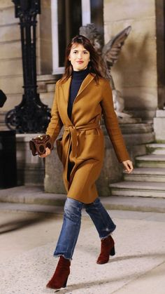 Jeanne Damas in a brown tie jacket, turtleneck, cropped frayed jeans, and burgundy booties