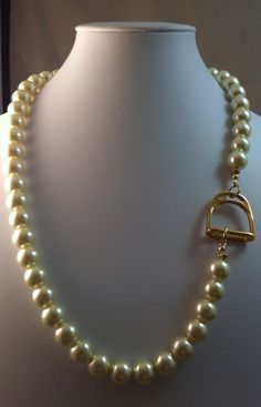 Elegant is the word to describe this equestrian necklace. The finest glass 10mm ivory glass pearls made by Swarovski frame the hand plated gold