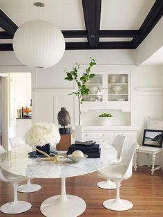 Large round pendant works well with white alls and the rounded shapes of saarient table and chairs.