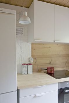 Wooden counter top and white kitchen with minimal is handles