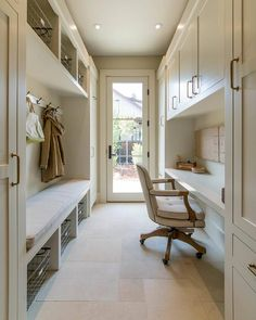 A glass patio doors opens to a long galley style mudroom featuring a white built in mudroom bench topped with a light gray cushion positioned above vintage metal baskets while a row of coat hooks are mounted above the bench flanked by long paneled cabinets adorning brass pulls.